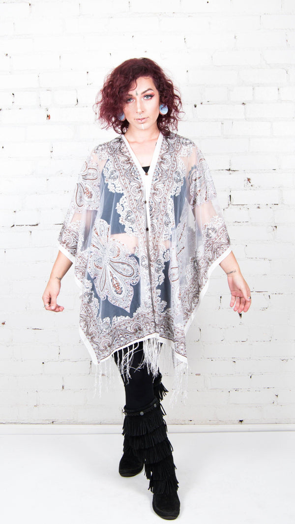 girl wearing white gypsy poncho with fringe festival fashion