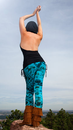 Girl on rocky mountain top wearing a hooded black top, diamond design tie dye leggings, brown suede fringe mocassins