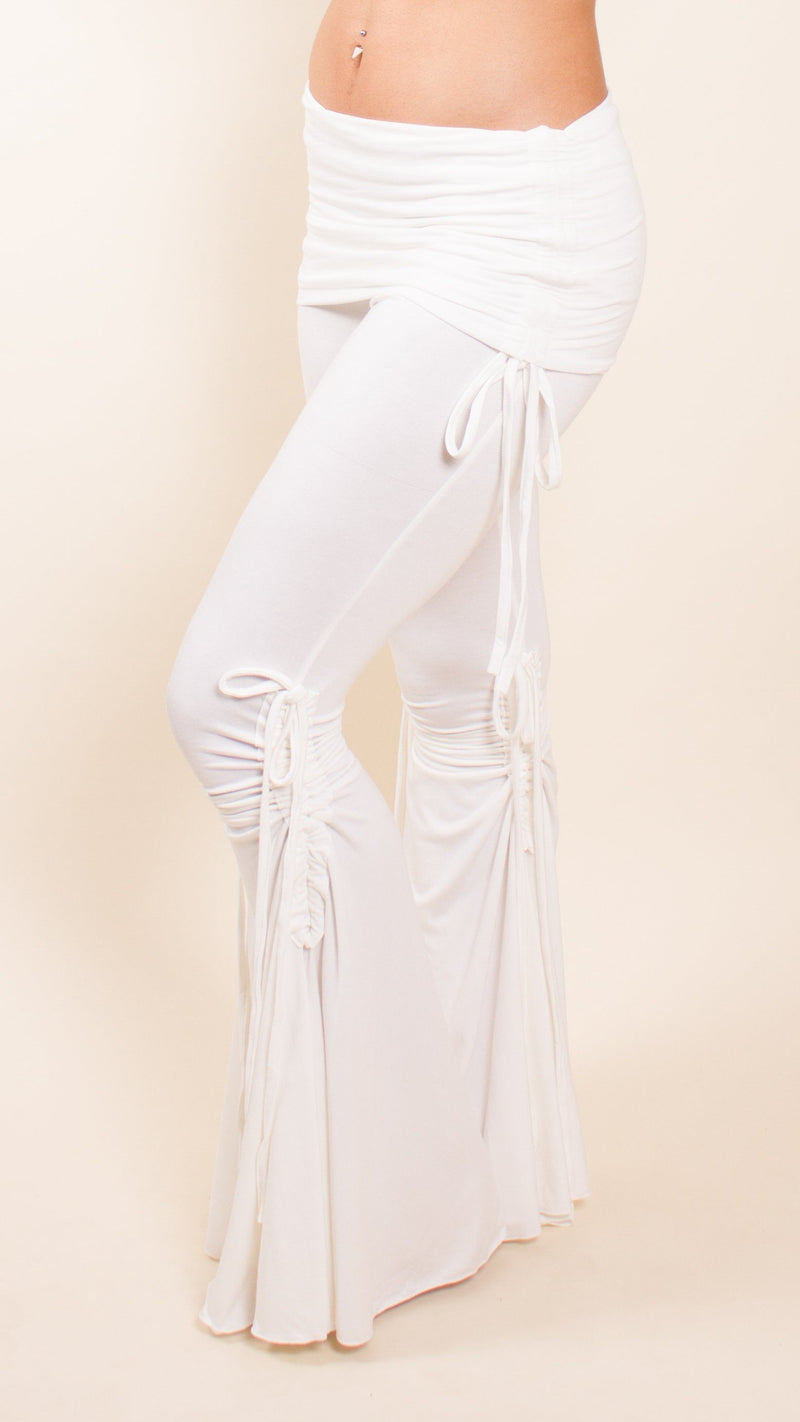 Girl wearing Umba's Bell Bottom Tie Pants with fold over skirt waistband and cinched ties on inner and outer legs and hips, white, front side view, sold at UMBA LOVE.