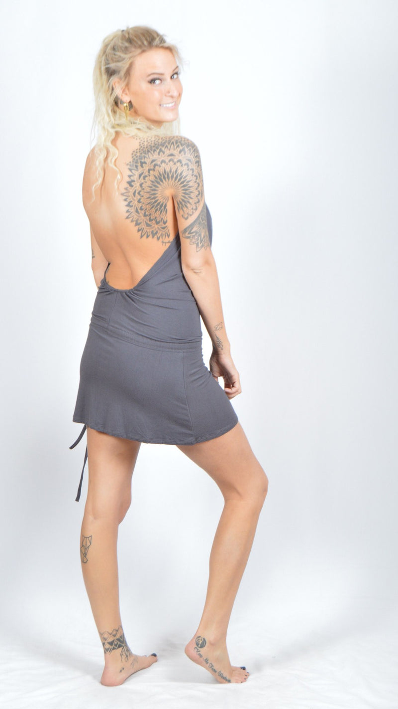 Girl wearing Umba Backless Cowl Neck Dress, cinched sides, charcoal, back side view, white brick background, sold at UMBA LOVE.