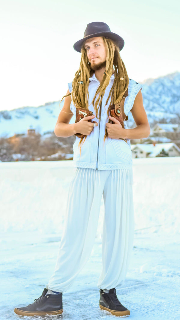 man with dreadlocks wearing white harem meditation pants, hand made leather holster, flower of life vest