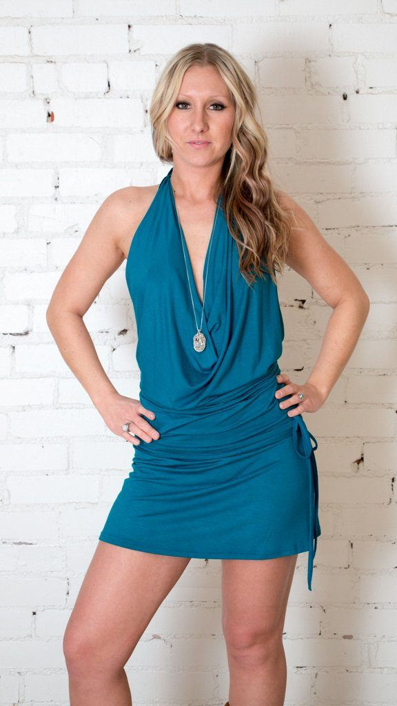 Girl wearing Umba Backless Cowl Neck Dress, cinched sides, dark teal, white brick background, sold at UMBA LOVE.