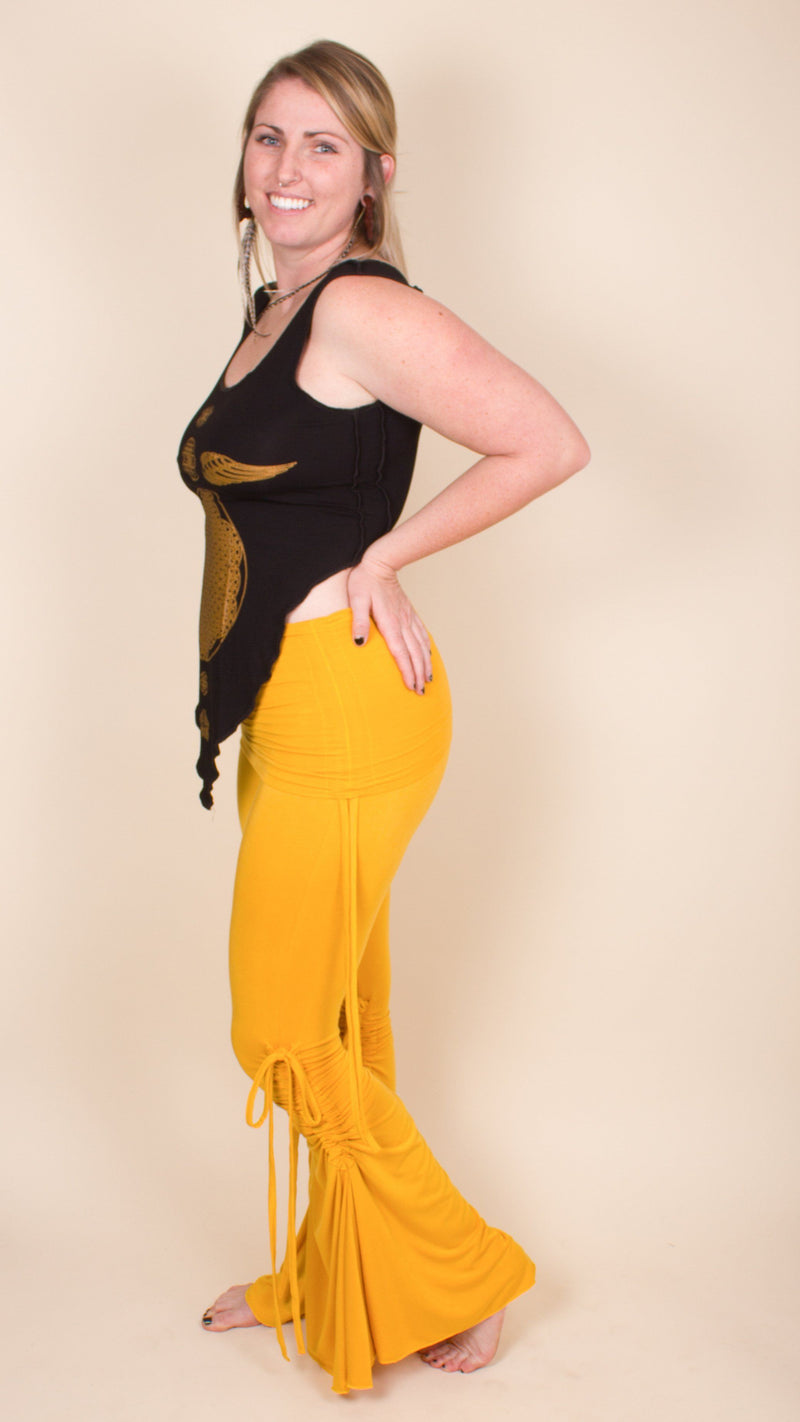 Girl wearing Umba's Bell Bottom Tie Pants with fold over skirt waistband and cinched ties on inner and outer legs and hips, yellow, side view, sold at UMBA LOVE.