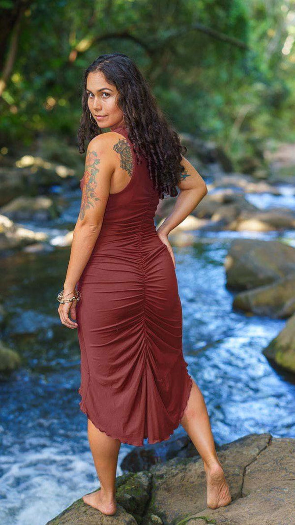 Girl standing on rock by river wearing Nectar Creations Bella Dress, sleeveless cowl neck, ruched back and asymmetrical hemline, burgundy, back view, sold at UMBA LOVE.
