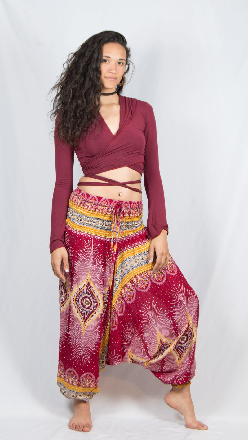 Girl wearing Umba Festival Fashions, cherry red feather harem pants and maroon long sleeved thumbhole hoodie, front view, sold at Umba Love.
