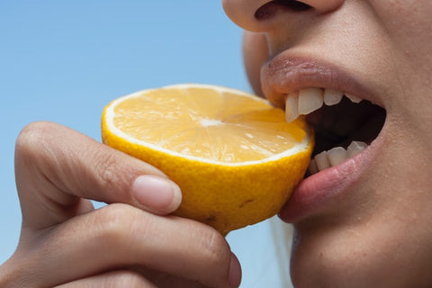 woman biting into half a lemon