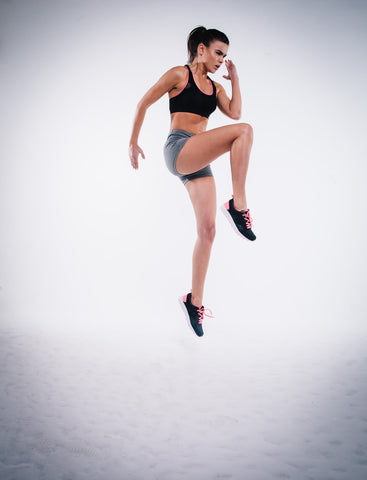 Woman jumping high off the ground with knees extended