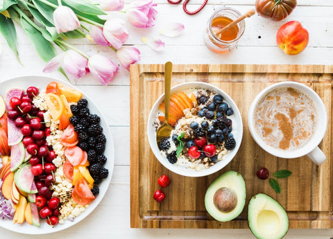A table of smoothie bowls, honey, and fruit