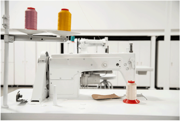 A white backdrop, complete with the hand-painted sewing machines, is intended to make the colors of the craft pop.