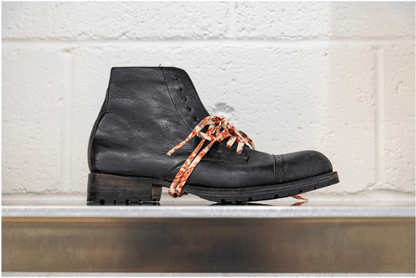 A unisex, black leather Esquivel boot with handmade laces on display in the designer's showroom.