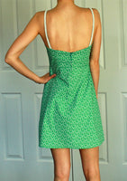 Short flower printed green dress with lowered back neckline with thin white straps.