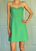 Short flower printed green dress. It has a sweet heart neckline with thin white straps.