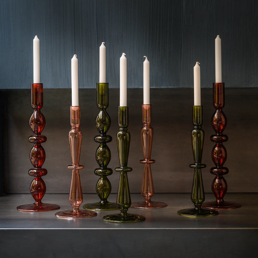 All our recycled glass candle holders next to each other displayed in  front of a dark wall