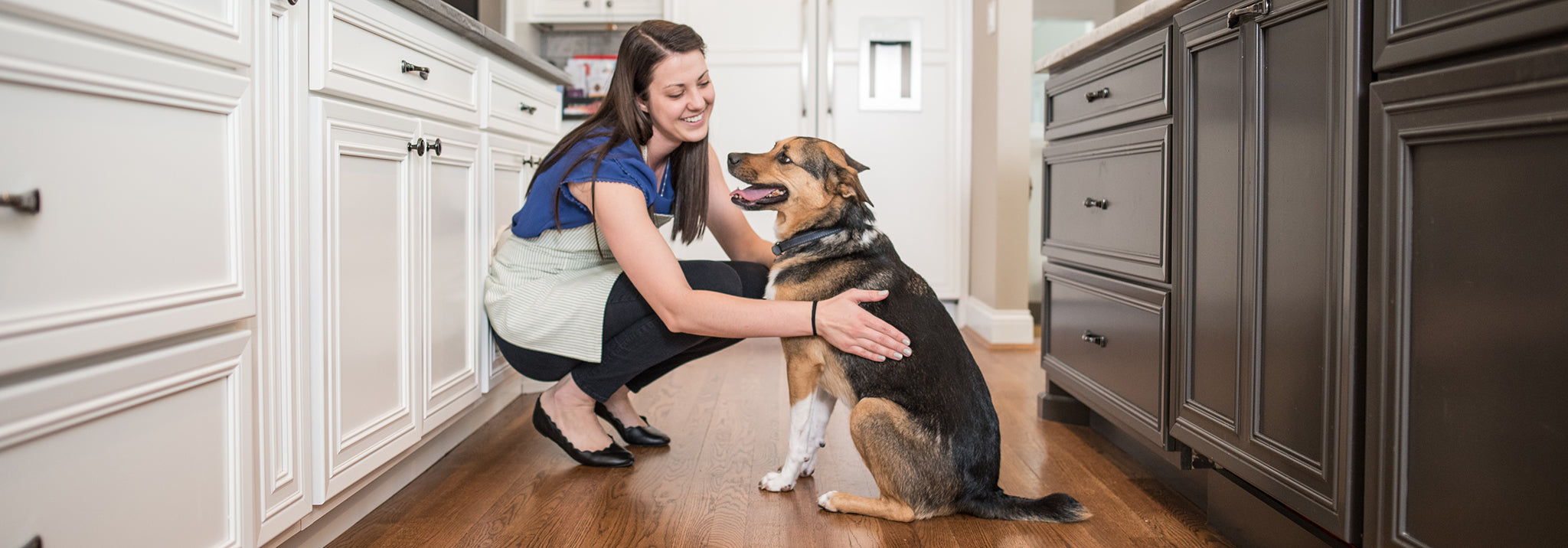 Woman wearing an apron petting her dog in the kitchen.