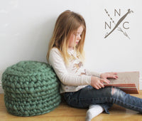 girl sitting beside cushion made from Mama Knows Luxury Naturally Nora Extreme Finger Crochet Cushion Kit