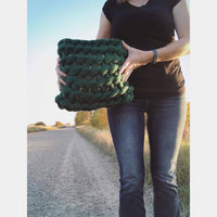 Woman holding cushion made from Mama Knows Luxury All About Ami Extreme Crochet Cushion Yarn & Pattern Kit