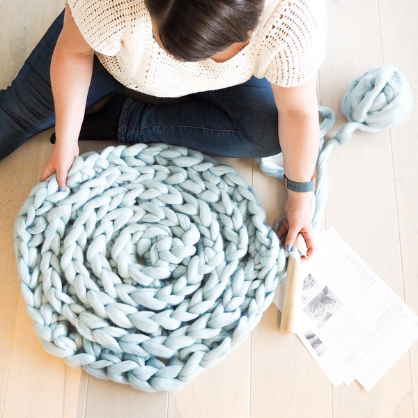 Woman with rug made from Mama Knows Luxury All About Ami Extreme Crochet Rug Yarn and Pattern Kit