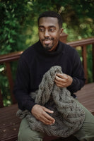 Man holding cowl made from Mama Knows Luxury Cable Mountains Cowl Knitting Kit