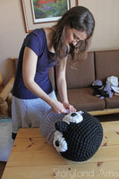 Woman making penguin made from Mama Knows Luxury Giant Penguin Amigurumi Yarn and Pattern Crochet Kit