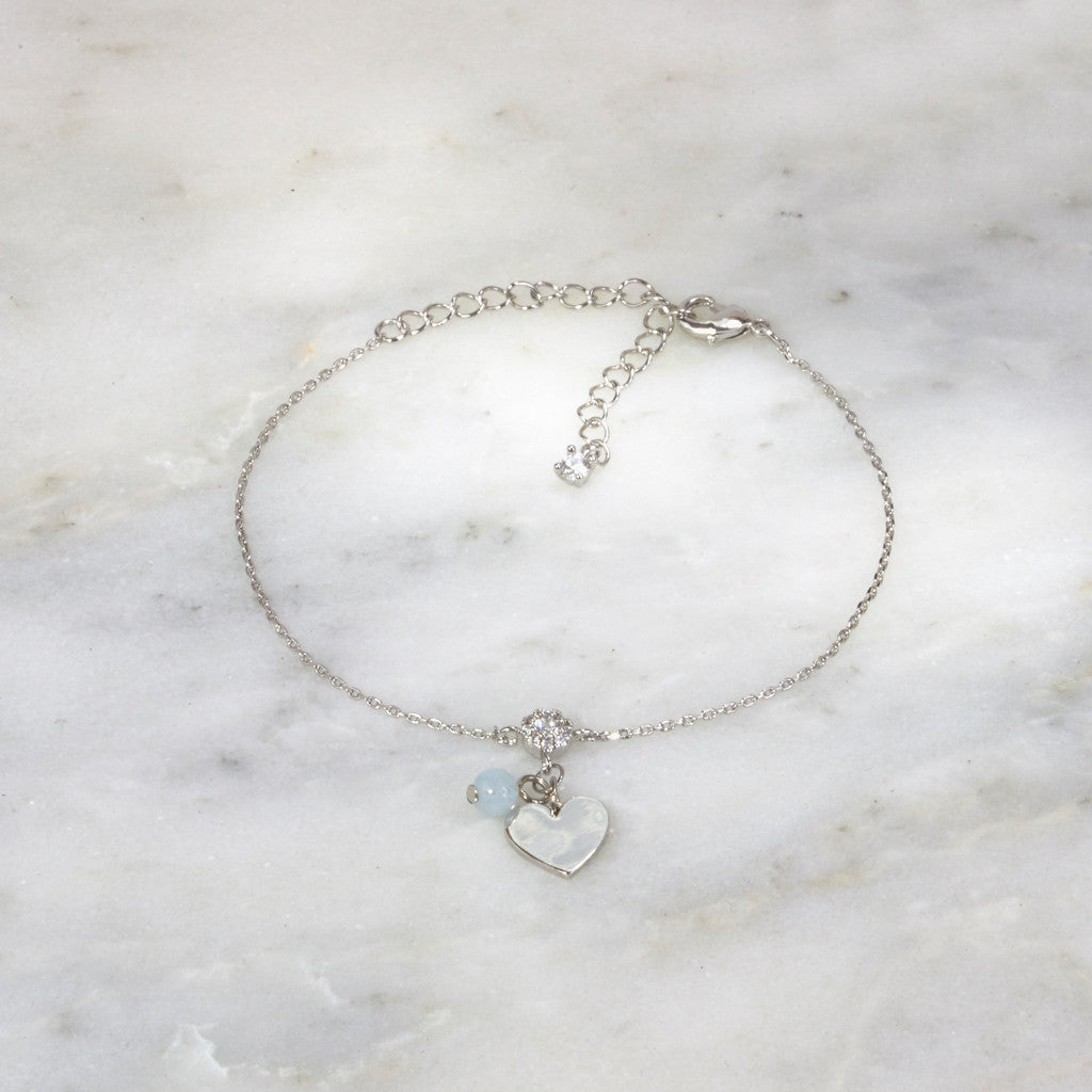 white gold heart charm bracelet on marble