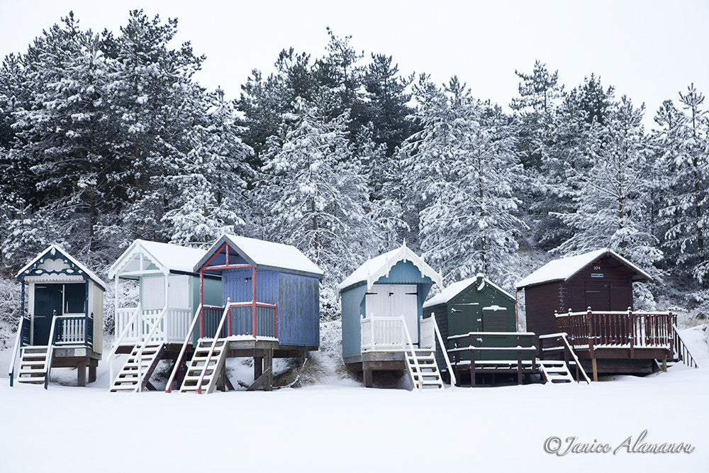 LSn767112 A Curve of Colourful Beach Huts brightens the Snow