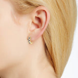 "Diamond and sapphire ""huggy"" style earrings in 18k yellow gold on ear"