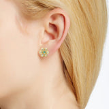 Diamond and emerald flower earring on ear