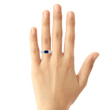 Bezel set oval cabochon sapphire and diamond ring in 18k gold on hand