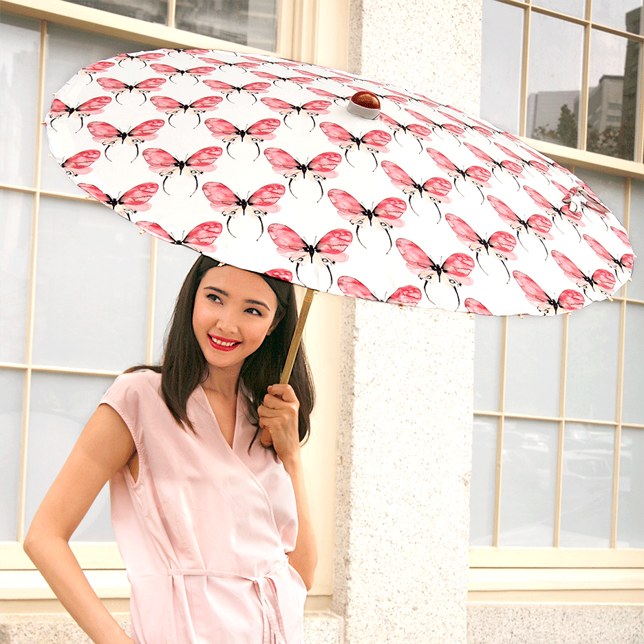 Woman carrying Lily-Lark rose and pink butterfly print handcrafted bamboo and fabric UV sun parasol / umbrella