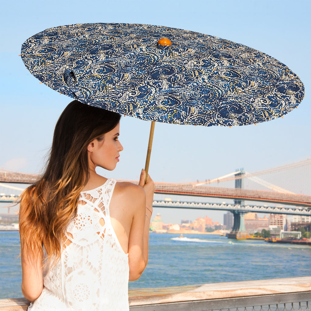 Woman carrying Lily-Lark blue and navy denim beads print handcrafted bamboo and fabric UV sun parasol / umbrella
