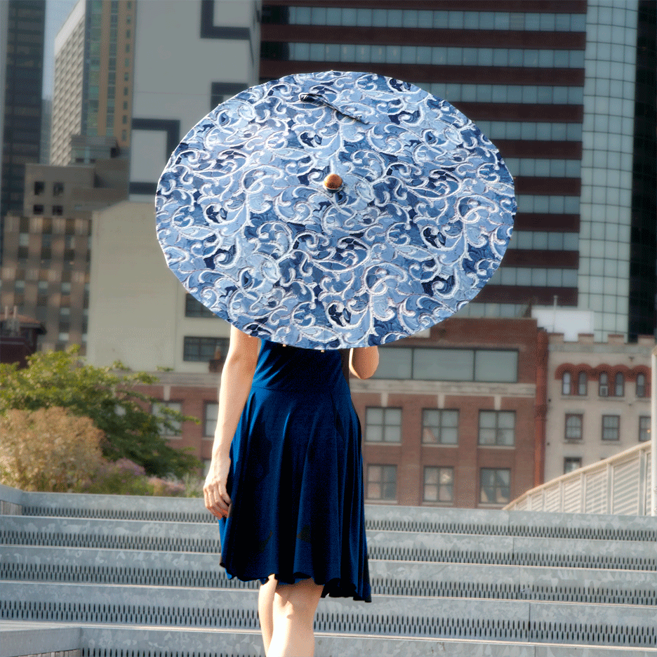 Woman carrying Lily-Lark navy and blue denim vine print handcrafted bamboo and fabric UV sun parasol / umbrella