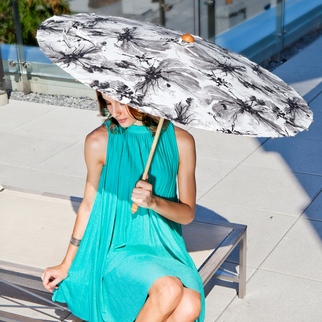 Woman carrying Lily-Lark black, grey and white ink wash flower print handcrafted bamboo and fabric UV sun parasol / umbrella