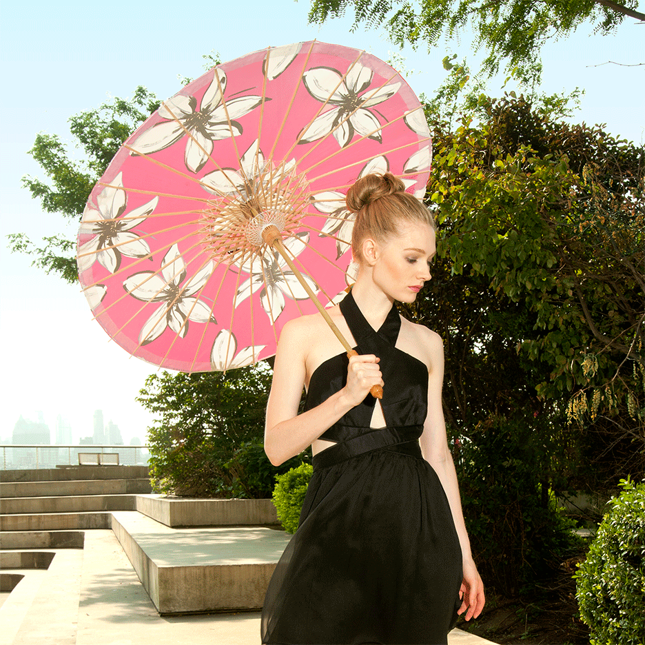 Woman carrying Lily-Lark pink mod flower print handcrafted bamboo and fabric UV sun parasol / umbrella