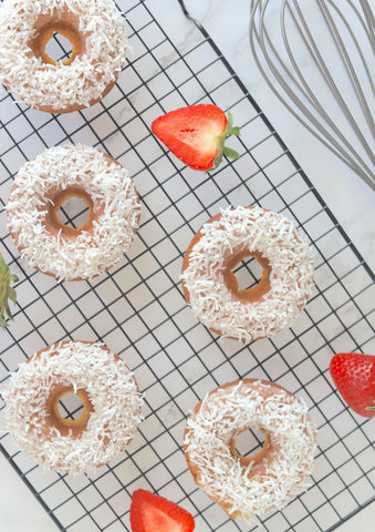 Strawberry coconut donuts on a cooling rack with fresh strawberries