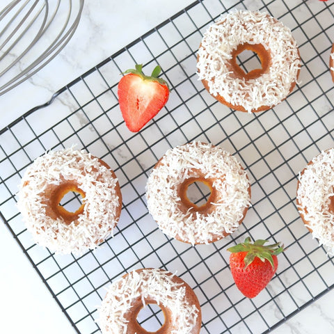 Strawberry coconut donuts on a cooking rack with fresh strawberries and a whisk