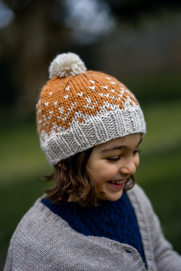 Happy child wearing ACORN KIDS Snowflake Beanie - Caramel & Oatmeal