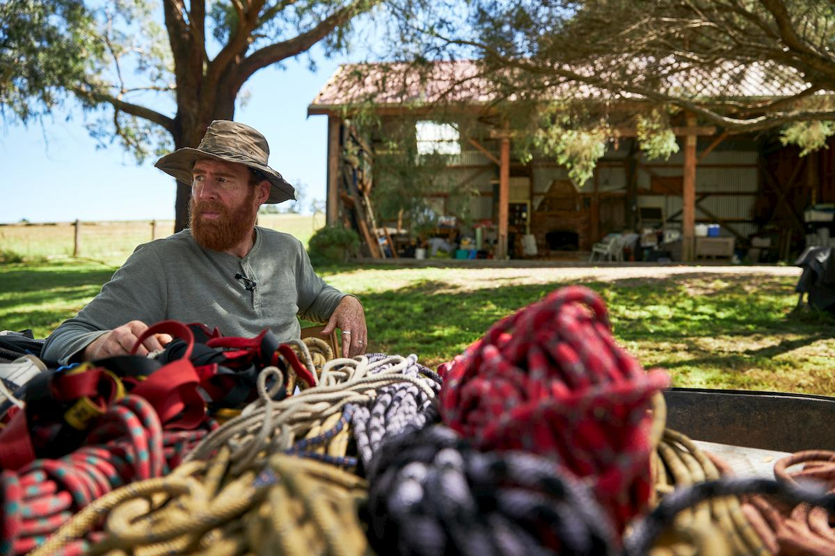 Beau Miles sitting in his backyard, contemplating his tree climb, surrounded by ropes.
