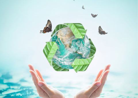 a womans hands are around a recycled symbol around a globe with butterflies flying around it