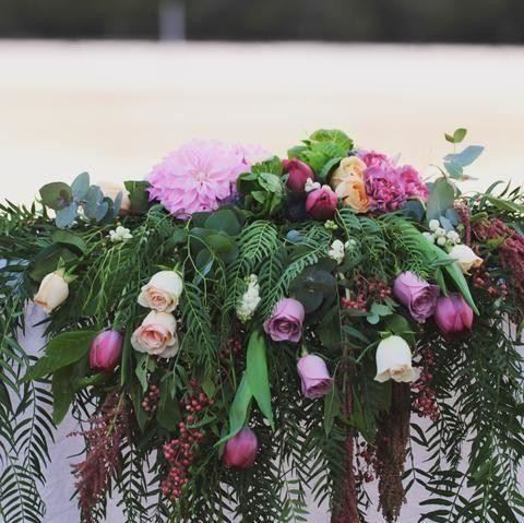 Long flowing bridal table arrangement with peppercorn, roses, tulips, kale and dahlia