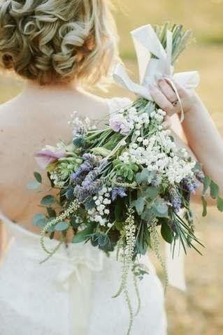 Bride holding bouquet behind her back. Wedding bouquet features lavender, babies breath, succulents, calla Lilly, ruscus, budlea, purple and white, garden style