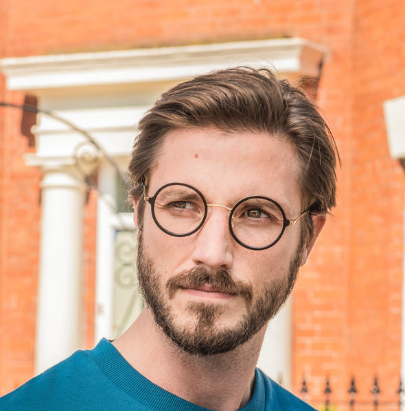 Ryan wears Poppy round frames in black from the William Morris Gallery Collection