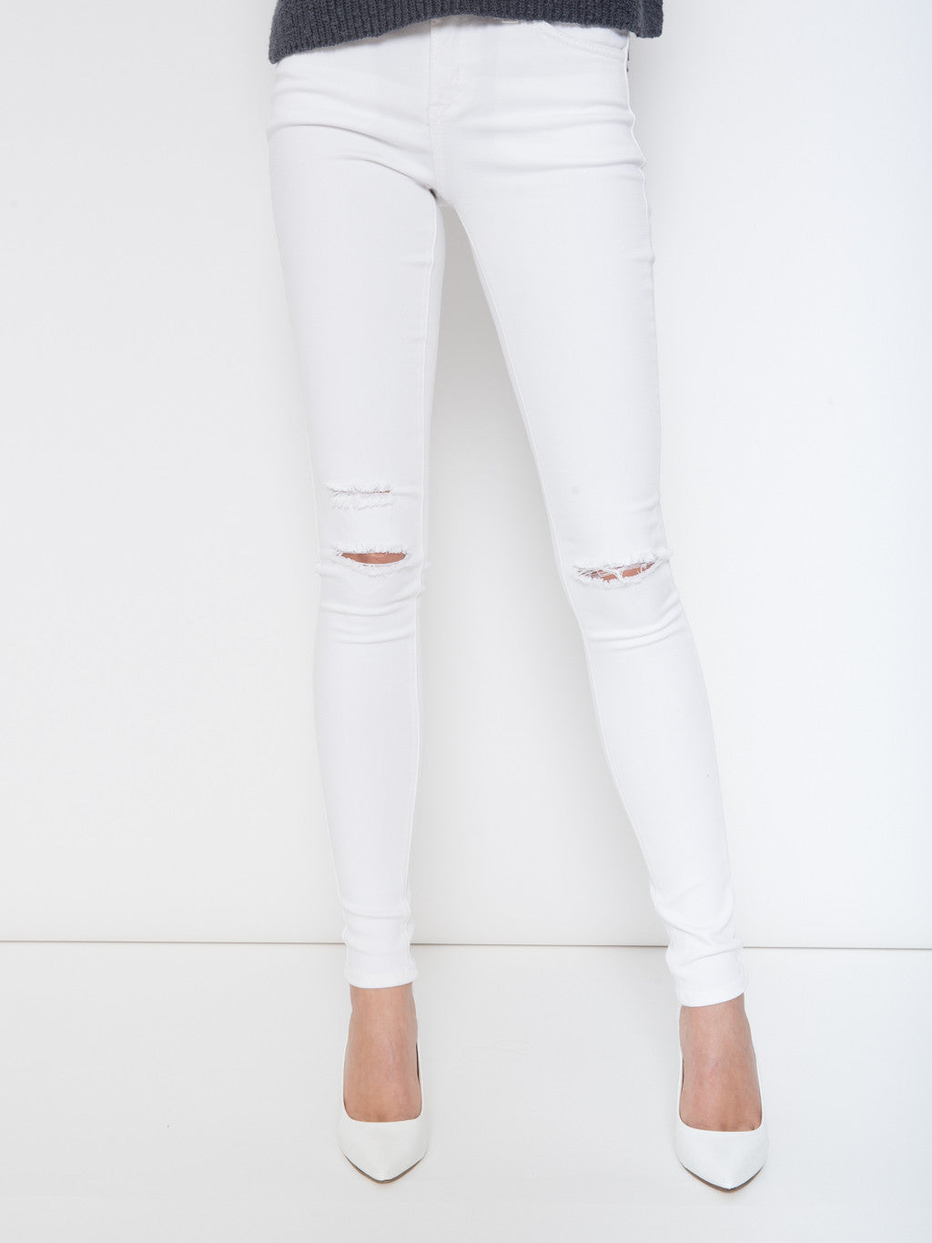 Kancan distressed white denim skinny jeans featuring a single button fastening, zip fly, standard belt loop, two front pockets, and two rear pockets. Asymmetrical knee distress keeps eyes away from any problem areas and directs attention to your lean legs and pretty shoes.