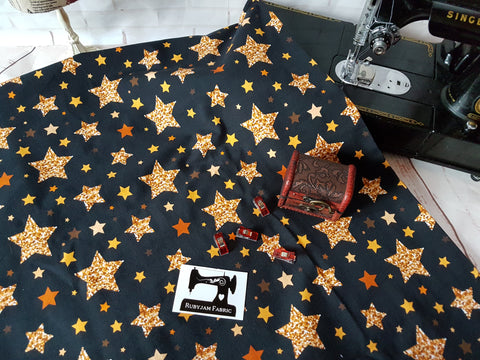 Gold Stars on Black cotton lycra 4 way stretch knit fabric