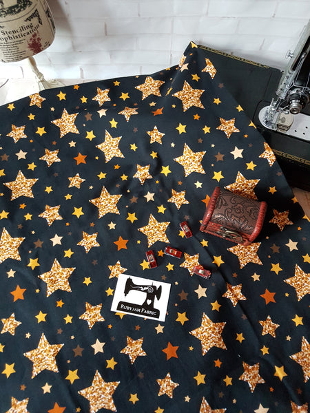 Gold Stars on Black - cotton lycra - 150cm wide