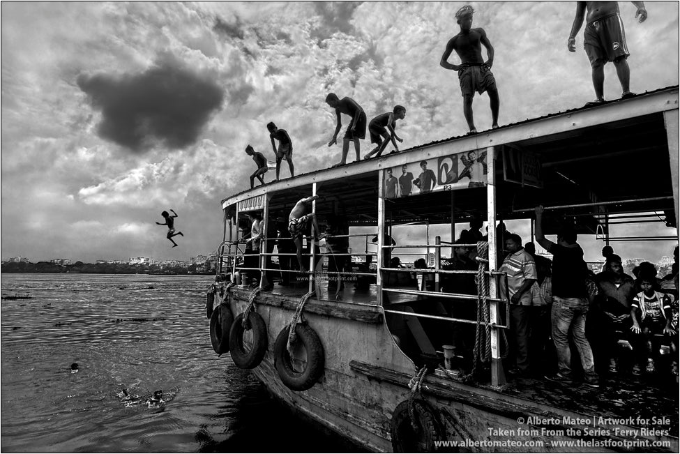 Ferry riders diving from the roof of a ship, Kolkata, India.