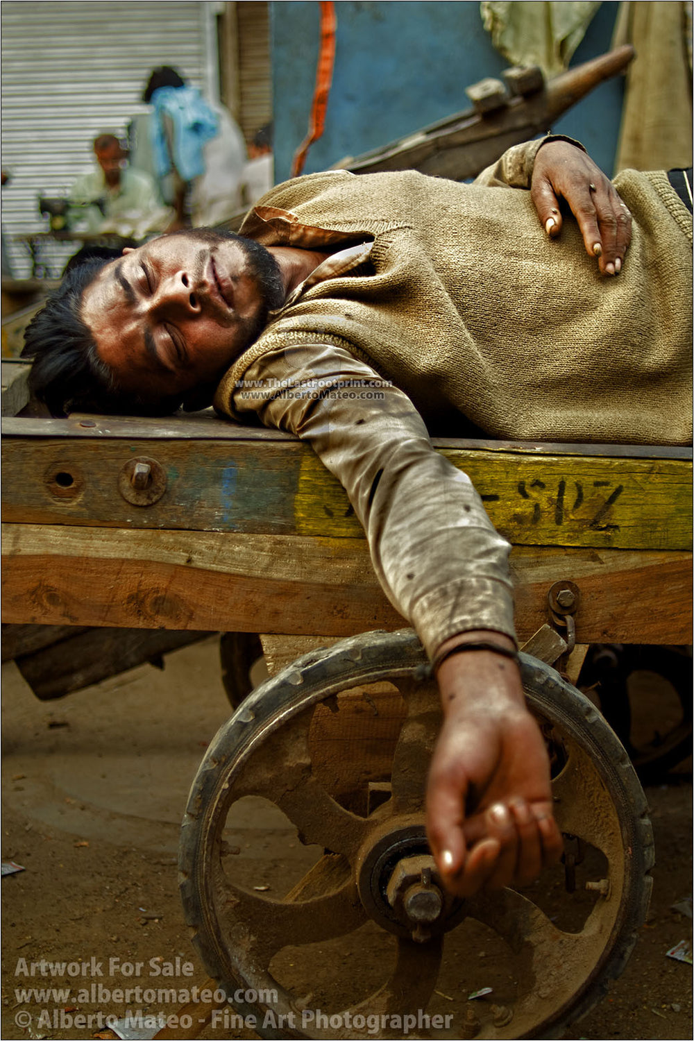 Carrier taking a nap on delivery charriot, Old Delhi. | By Alberto Mateo.