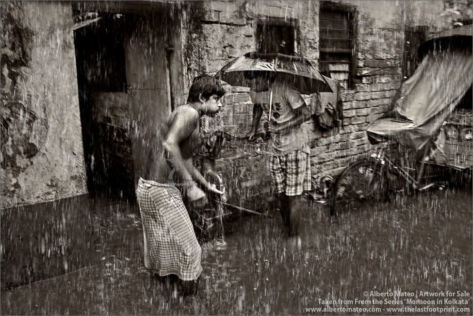 Men getting water from well under the rain, Kolkata, Bengal, India.