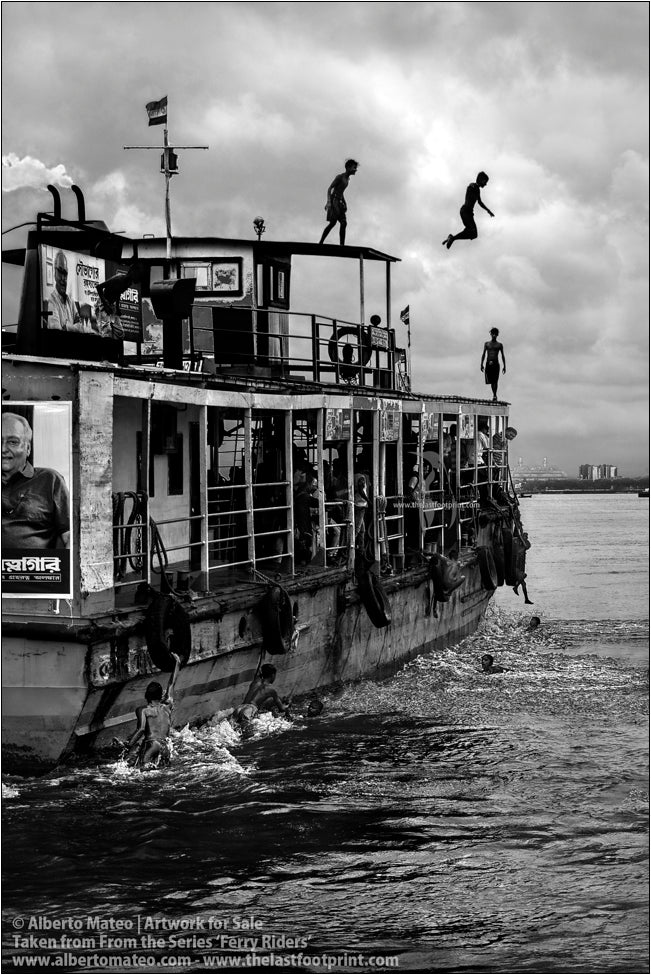 Boys diving from the roof of ship, Hooghly River, Kolkata, India.