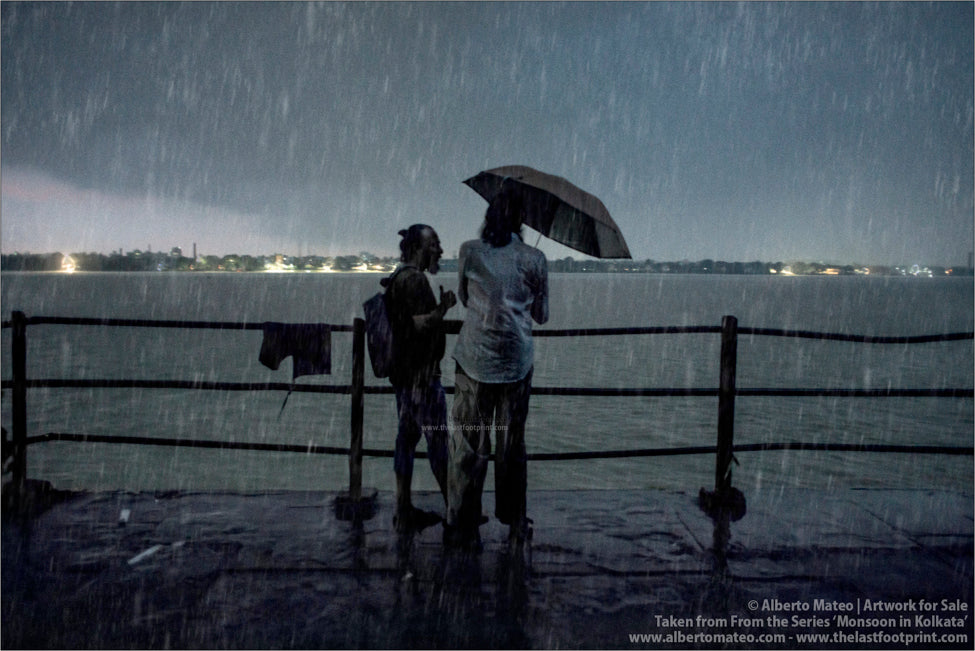Two men chatting under umbrella, Hooghly River, Kolkata, Bengal, India.