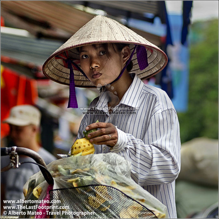 Girl selling pineapples, Hanoi, Vietnam. | Square crop.